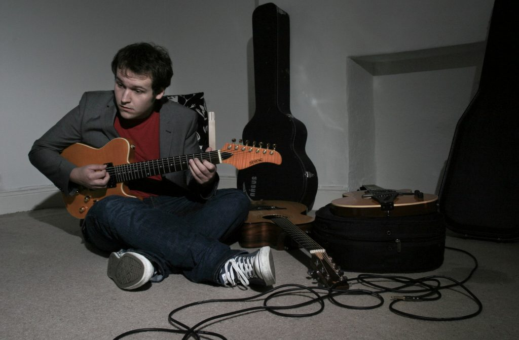 Edd plays guitar cross legged.  He raises his eyebrows mid-riff.