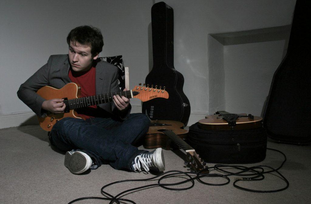 Edd plays guitar cross legged.  He raises his eyebrows mid-riff.