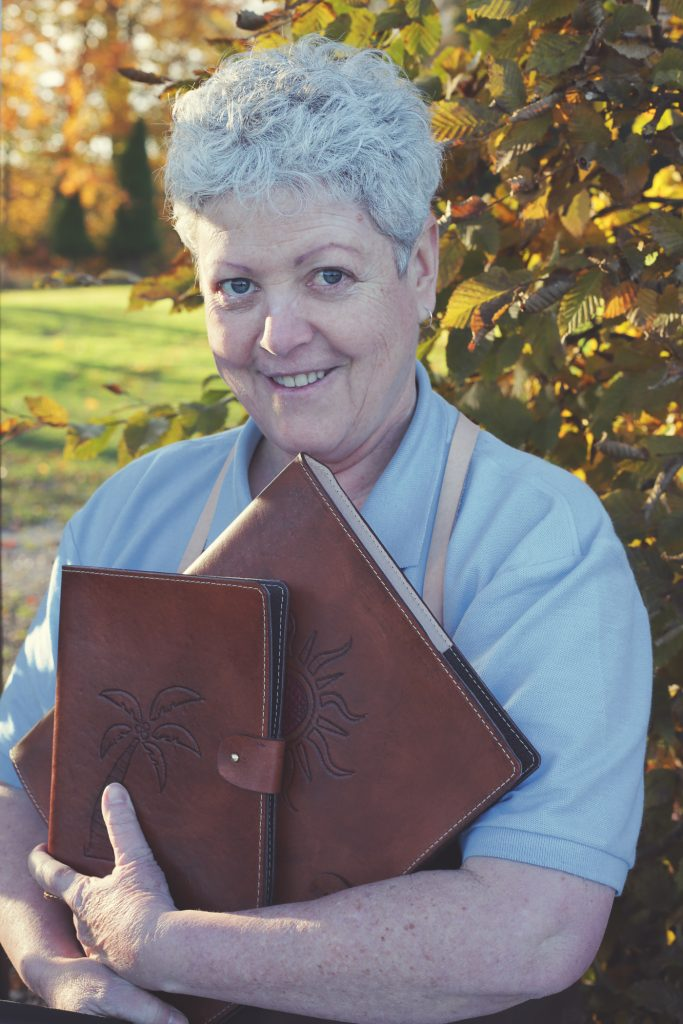 Philippa holds her RAW Leatherworks Creations in the low Autumnal light