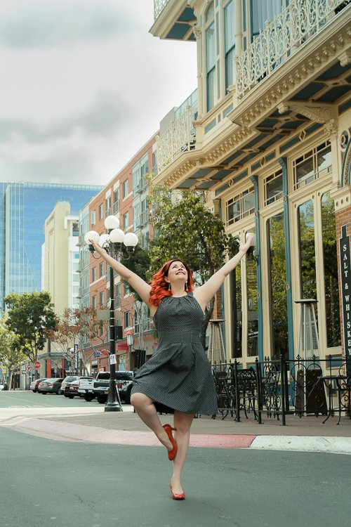 Christine holds Yogic Tree Pose in the middle of the San Diego Street in heels and a smart dress looking up to the sky with glee and joy