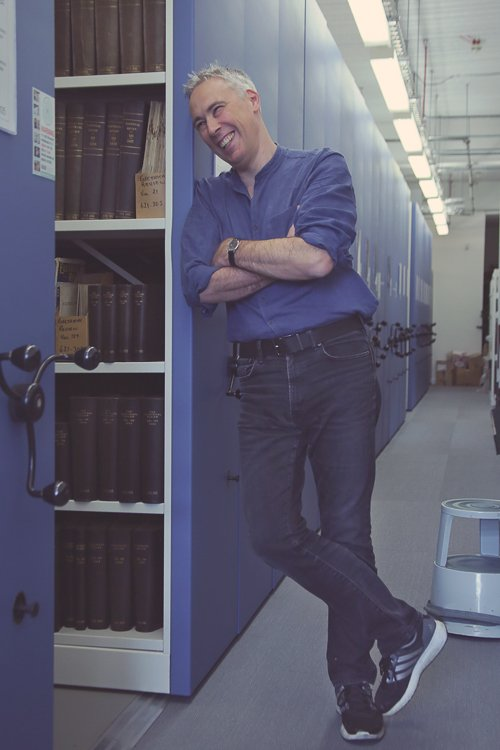 Simon leans against a library archaving shelf in Newcastle City Library and laughs, dressed casually for his professional photography headshots session