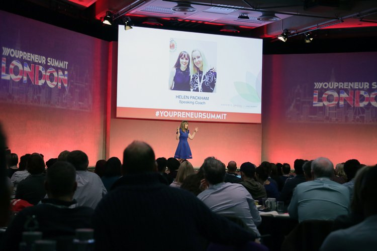 Janet raises both hands to indicate her appreciation for her personal speaking coach Helen Packham (shown in slide above) as she is mid-stage at the enormous Youpreneur Summit holding the crowd's attention.  The picture of personal achievement at a Professional Speaker.