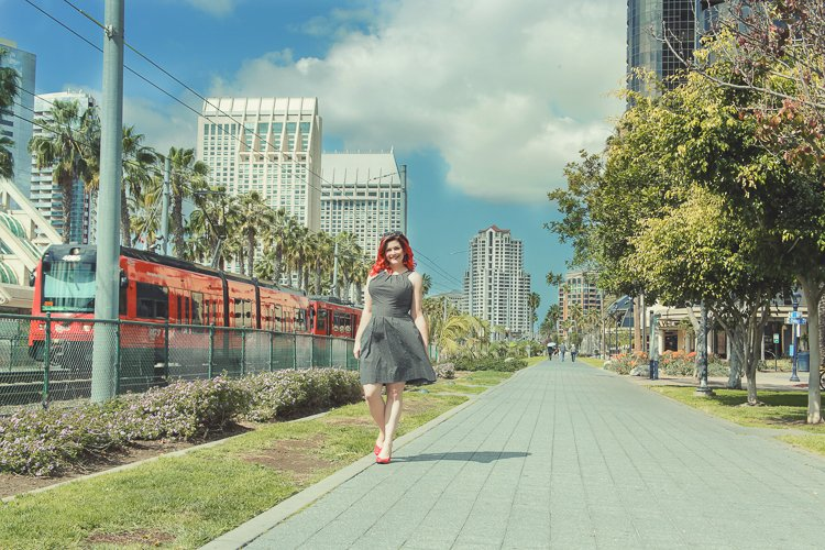 Walking with powerful San Diego Trains, Christine walks in tandem with the Red Trolley for her San Diego Headshot by Laura Pearman Photography